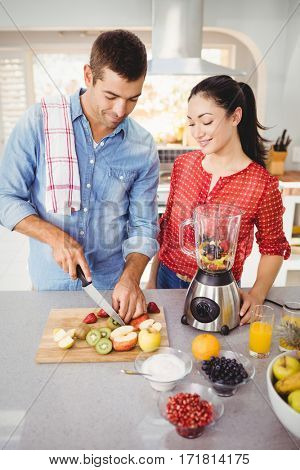 Couple preparing fruit juice while standing at table in home