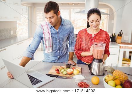 Couple standing with fruit juice while man using laptop at home