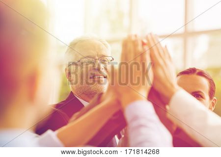 business, people and teamwork concept - smiling business people making high five in office