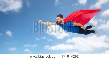 freedom, power, motion and people concept - happy man in red superhero cape flying in air over blue sky and clouds background