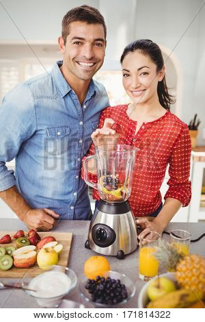 Portrait of smiling couple preparing fruit juice while standing at table in home