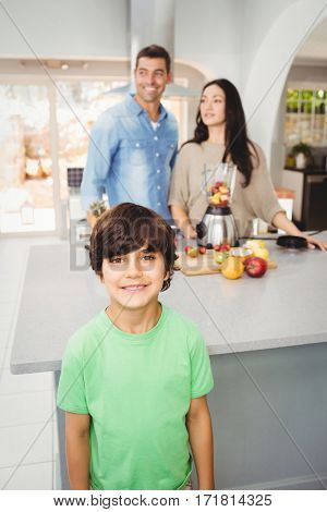 Smiling boy with parents preparing fruit juice at home