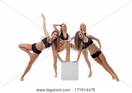 Pretty girls in black tops and shorts posing by the cube studio shot