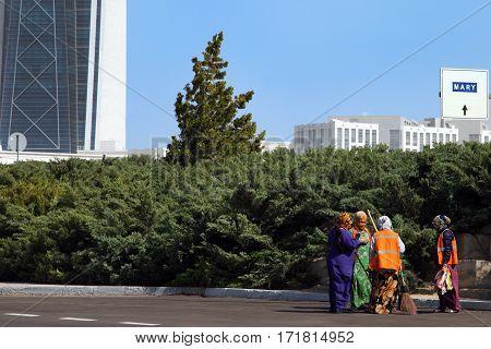 Ashgabat Turkmenistan - October 26 2014. Women clean the streets having fun talking to each other. Ashgabat Turkmenistan - October 26 2014.