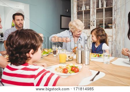 Smiling family with grandparents sitting at dining table in home