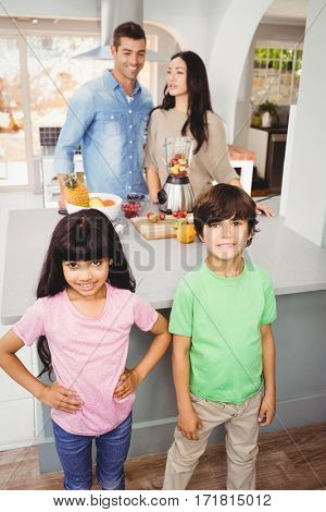 Siblings standing at table with parents preparing fruit juice in background
