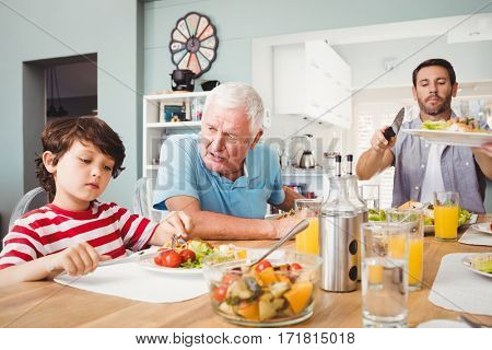 Granddad talking to grandson while sitting at dining table with family
