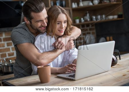 Smiling young couple hugging and using laptop in kitchen