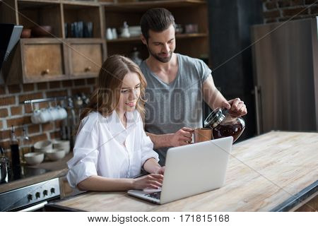 Smiling young couple drinking coffee while using laptop in kitchen