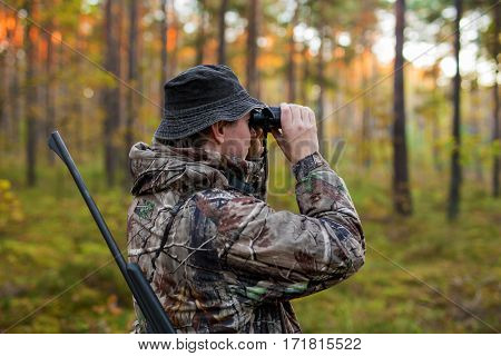 Hunter observing forest with binoculars for hunting session