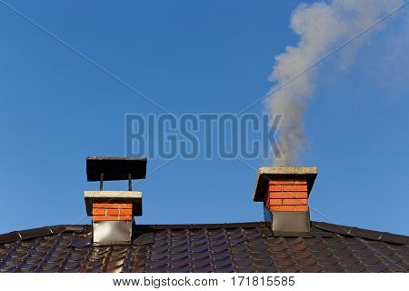 Smoke from brick chimney on the roof against the blue sky