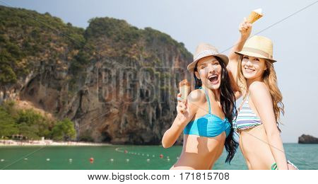 summer holidays, vacation, food, travel and people concept - smiling young women eating ice cream on beach over bali beach and rock background