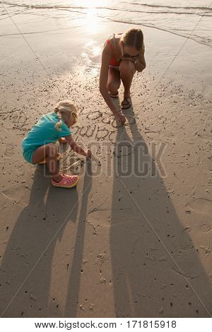 Mother and baby girl drawing on sandy beach