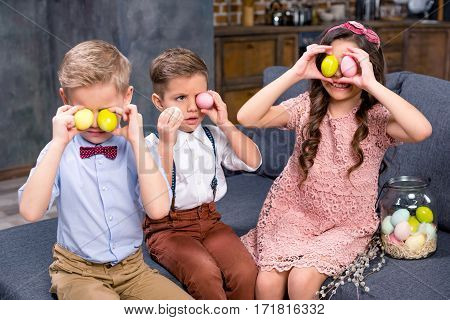 Two little boys and girl sitting on sofa and playing with Easter eggs