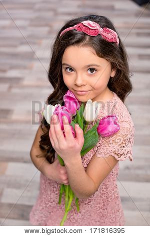 Gorgeous little girl holding bouquet of fresh tulip flowers and smiling at camera