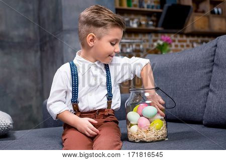 Little boy sitting on sofa with glass jar full of Easter eggs