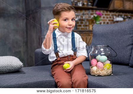 Little boy sitting on sofa and playing with Easter eggs