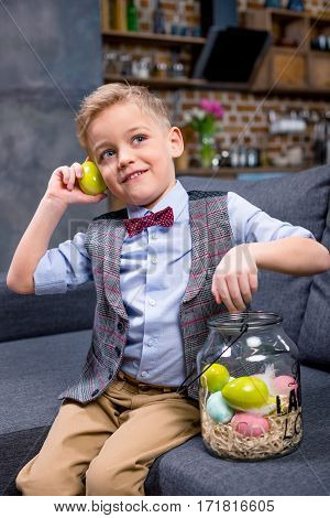 Cute little boy sitting on sofa and playing with Easter eggs