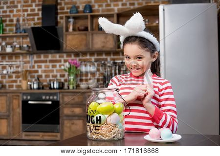 Adorable little girl in bunny ears holding white feather and smiling at camera