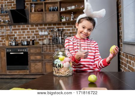 Smiling little girl in bunny ears holding easter egg and showing thumb up