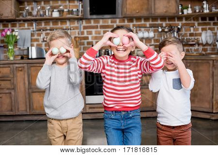 Three cute laughing kids playing with easter eggs in kitchen