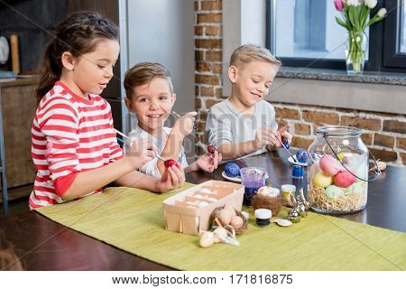 Three adorable little kids painting easter eggs together