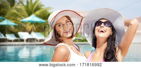 summer holidays, vacation, travel and people concept - smiling young women in hats and casual clothes over exotic beach with palm trees and pool background