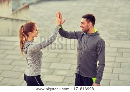 fitness, sport, gesture, people and success concept - happy couple giving high five outdoors