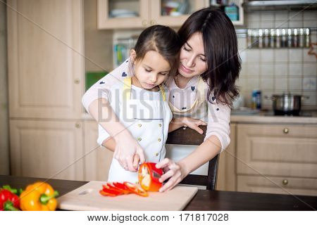 Mother and daughter cooking at the kitchen