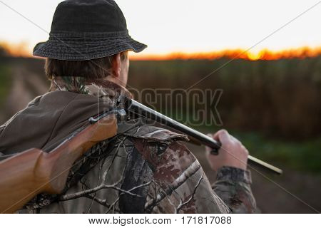 Hunter with rifle over his shoulder and walking