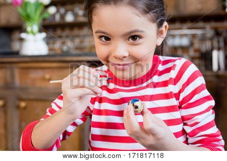 Beautiful little girl painting easter egg and smiling at camera