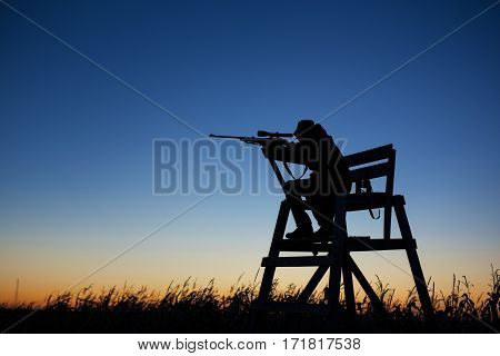 Hunter in lookout tower by dusk with gun