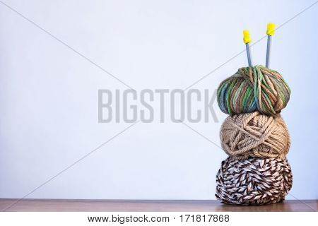 Three Threads For Knitting White And Brown Colors And Spokes On Wooden Brown Table On White Background Copyspace.