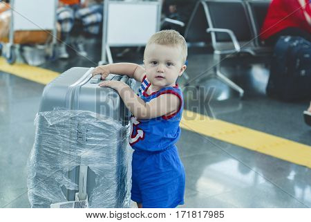 Little Boy in blue suit with silver suitcase at the airport