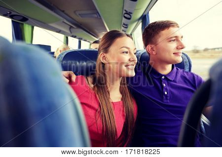 transport, tourism, road trip and people concept - happy teenage couple or tourists hugging in travel bus and looking through window