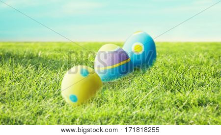 easter, holidays, tradition and object concept - close up of colored easter eggs and decorative grass on wooden surface over blue sky and grass background