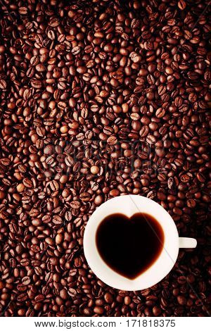 Heart shape coffee cup on coffee beans