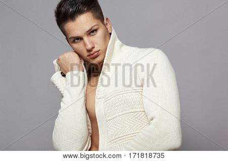 young man in a white a jacket on a gray background
