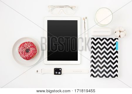 Top view of white female office table with laptop, notebook, wrist watch, pen, pencil, glasses, milk