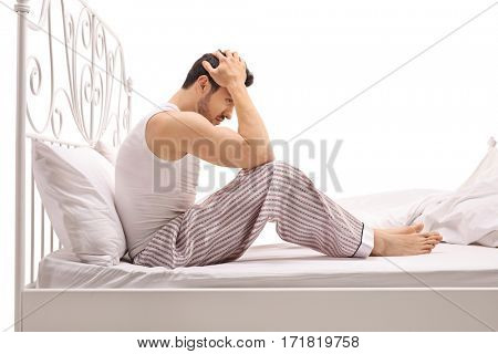 Depressed man sitting on a bed with his head down isolated on white background