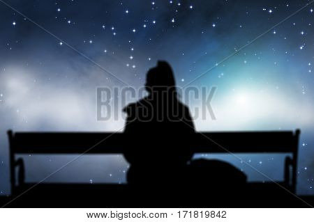 Lonely girl watching stars while sitting on a bench.