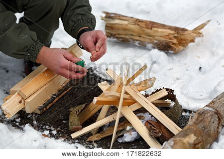 A man is going to strike a match to make a fire in the winter forest.