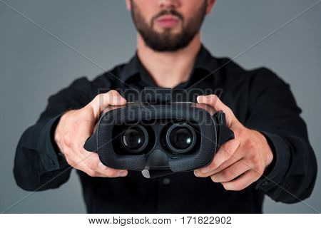 Man offers to wear glasses virtual reality, VR goggles, VR-headset glasses. A man on a gray background