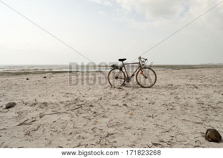 Red and white racing bike on the white sand of bamburi beach in Mombasa Kenya