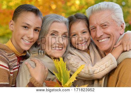 portrait of grandparents with grandchildren posing outdoors in autumn