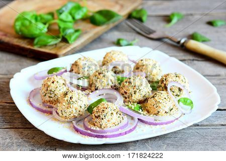 Small cheese balls on a plate. Cream cheese balls with dried herbs and roasted sesame seeds served with fresh onion rings and basil. Easy cheese snack food. Closeup