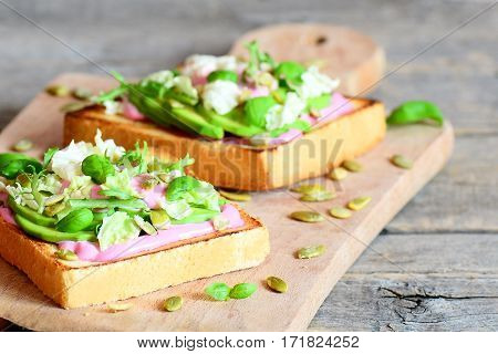 Avocado sandwiches on a wooden board. Homemade open sandwiches with avocado, pumpkin seeds, lettuce, basil and cream. Healthy eating. Vintage style. Closeup