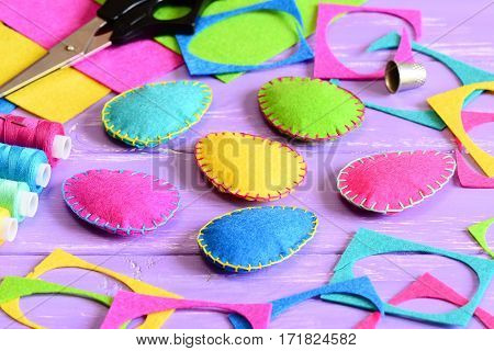 Colorful felt Easter eggs ornaments, felt sheets and scraps, scissors, thread, thimble on a table. Easy Easter crafts idea for kids. Easter craft background