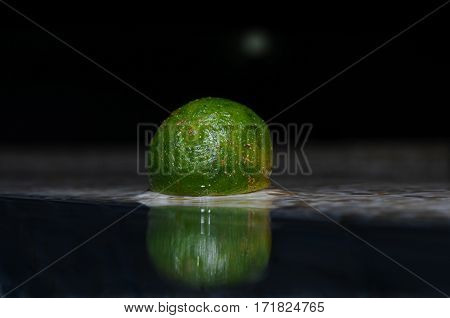 Reflection of a tiny lemonsito (kalamansi) in water, Panglao, Philippines