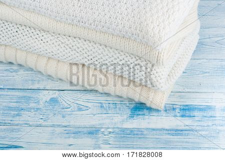 Knitted wool sweaters. Pile of knitted winter clothes on blue wooden background sweaters knitwear space for text